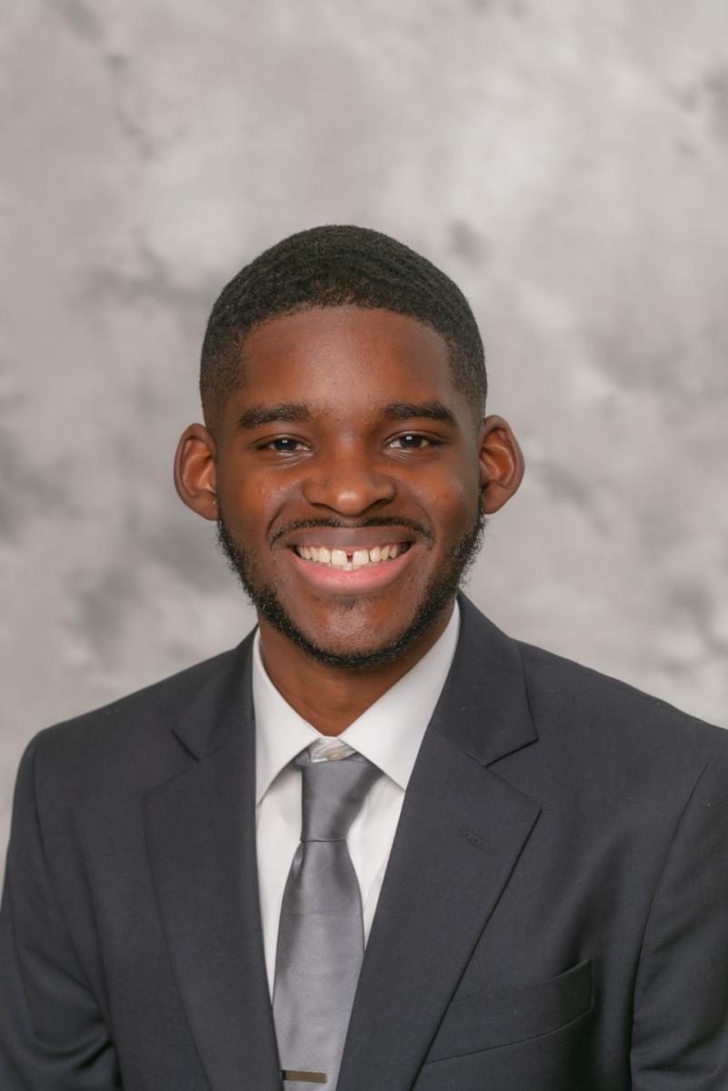 Headshot of speaker Joshua Simon in a black suit, gray tie, and white shirt.