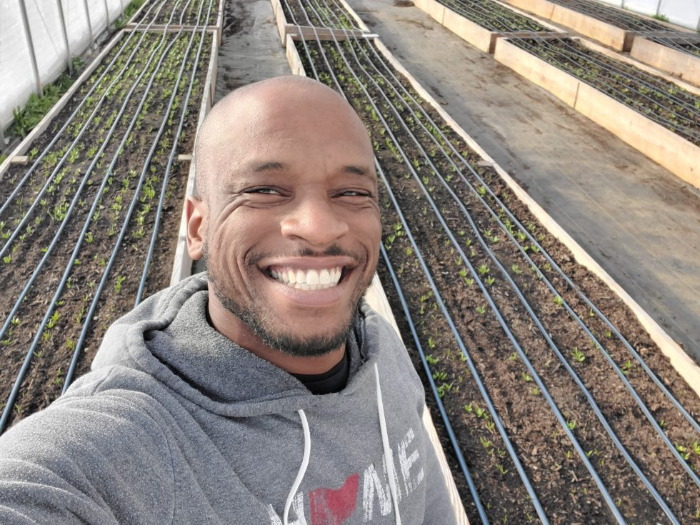 black man smiling in front of raised garden beds