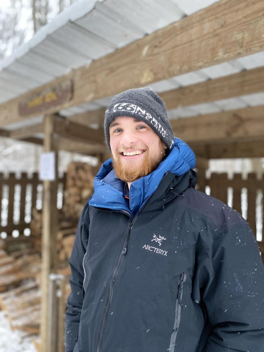 Image of Will in a blue jacket standing in front of a shed